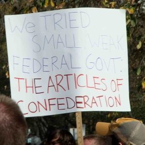 Protest sign saying that we already tried small, weak government under the Articles of Confederation.