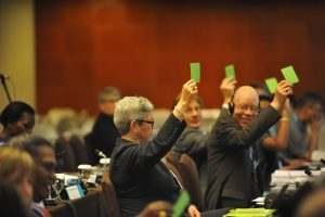 Committee members voting with green cards.