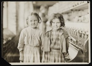 Two young girls working in a textile factory in 1909.