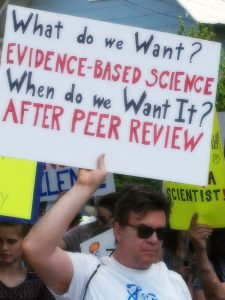 Demonstrator with a Sign Saying He Wants Evidence-Based Science