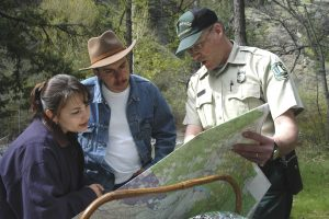 Forest ranger talking to hikers.