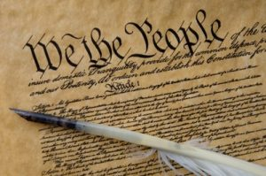 """historical document in tight cursive with """"We the People"""" at the top"""