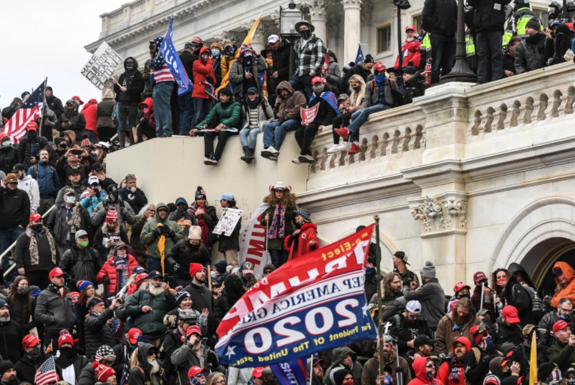 rioters sitting on and surrounding the US Capitol building and holding a Trump 2020 flag