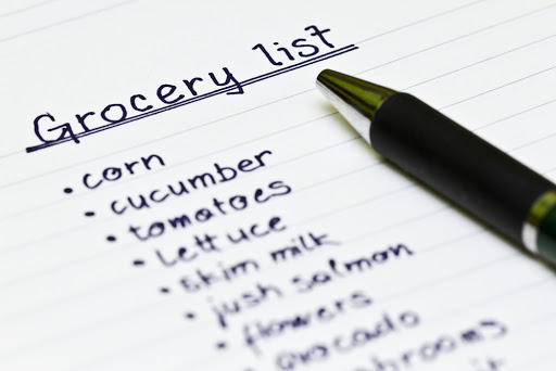 image shows pen and lined paper with grocery list of corn, cucumber, tomatoes, lettuce, skim milk, salmon, flowers, avocado, etc